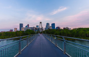 The Calgary skyline at sunset as seen from the pedestrian bridge on the north side of Prince's Island Park.