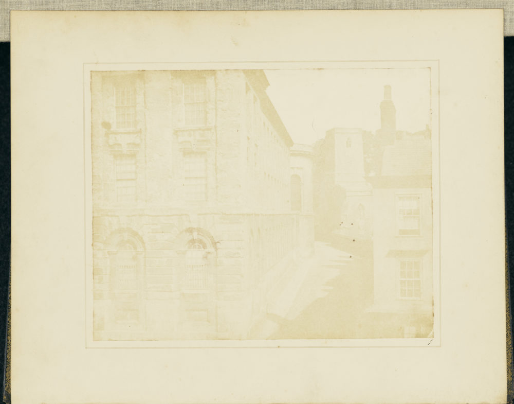 Plate I of Pencil of Nature - Part of Queen's College, Oxford. View of the side of a rusticated stone building with a narrow road down the right hand side. Used by permission under the Getty Museum Open Content Program.